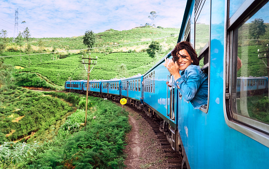 Happy smiling woman looks out from window traveling by train on most picturesque train road in Sri Lanka 952716620
