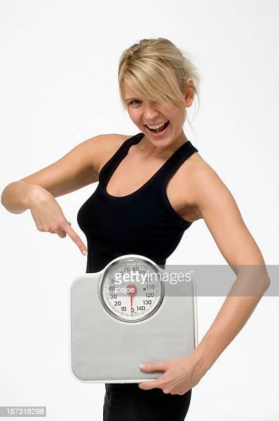 Feliz sonriente mujer señalando en báscula de baño