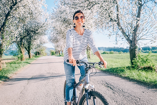 Happy smiling woman rides a bicycle on the country road under blossom trees. Spring is comming concept image. 1126268769