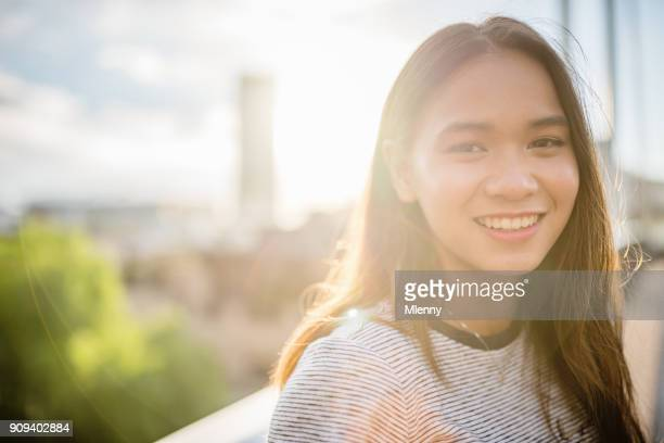 happy smiling young asian woman looking over - mlenny photography stock pictures, royalty-free photos & images