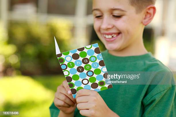 Happy smiling young boy reading a thank you card outdoors
