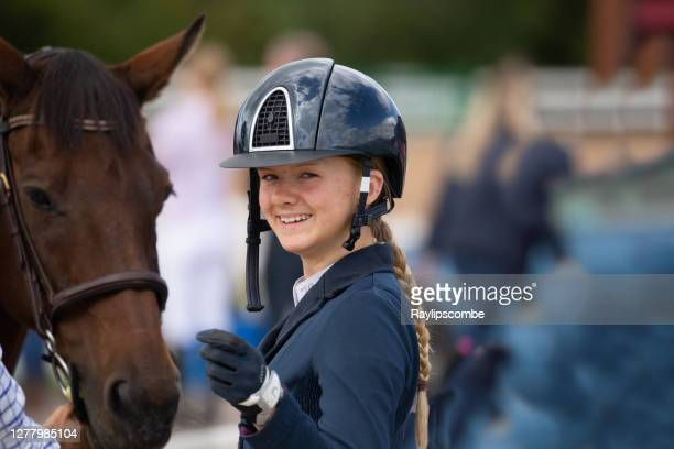 happy, smiling young horsewoman in a protective riding helmet stood by her horse. - equestrian event stock pictures, royalty-free photos & images