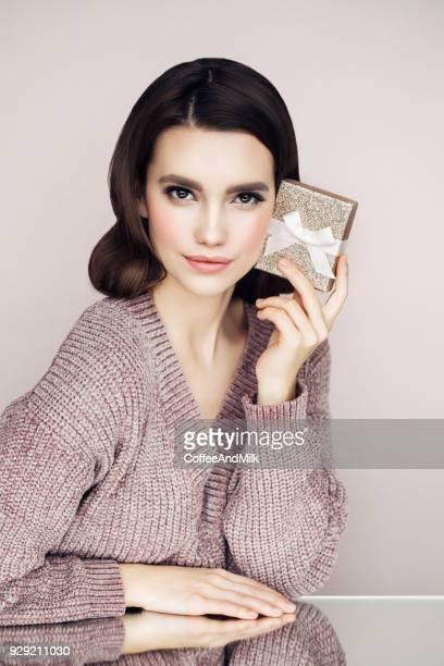 Heureuse souriante jeune femme détient sa boîte cadeau en mains