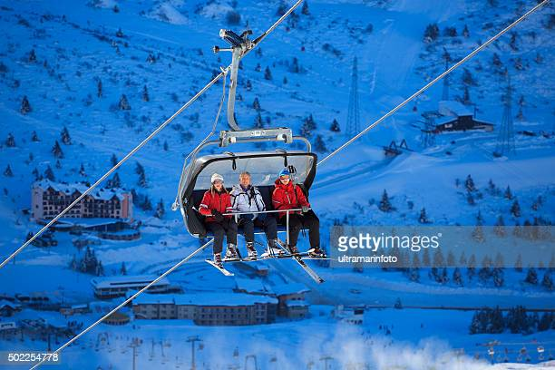 Happy snow skiers on the ski lift  going up