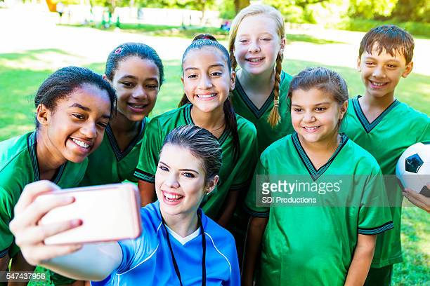 Happy soccer coach takes selfie with team