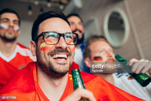 happy soccer fan with face paint holding beer - sports jersey stock pictures, royalty-free photos & images