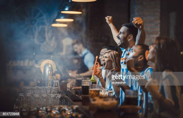 happy soccer fans cheering while watching a game in a bar. - mens world championship stock photos and pictures