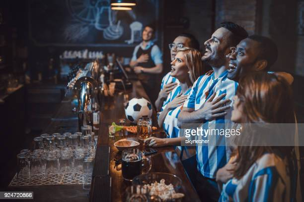 happy soccer fans singing the anthem before the game in a bar. - mens world championship stock photos and pictures