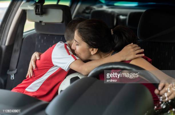 happy soccer mom dropping off her son to football practice and giving him a hug - sports training camp stock pictures, royalty-free photos & images