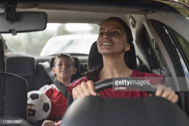 happy soccer mom transporting kid to football practice in her car - driver stock pictures, royalty-free photos & images