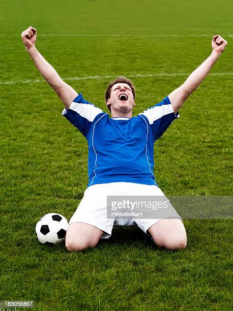 Happy soccer player celebrates victory with hands in the air