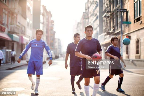 Happy soccer players walking at city street