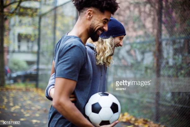 happy soccer players with ball talking on field - only young men stock pictures, royalty-free photos & images