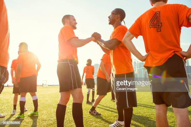 Happy soccer team on field during sunny day