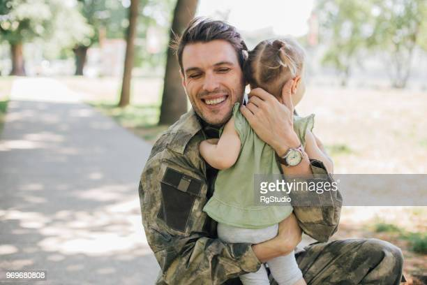 happy soldier in a hug with his young daughter - civilian stock pictures, royalty-free photos & images
