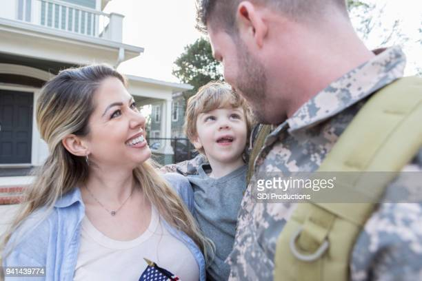 happy soldier is reunited with family - military spouse stock pictures, royalty-free photos & images
