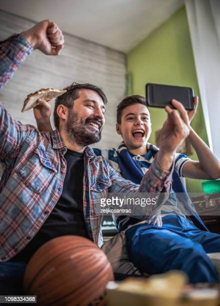 happy son and father cheering on basketball team and watching game at home - basketball sport stock pictures, royalty-free photos & images
