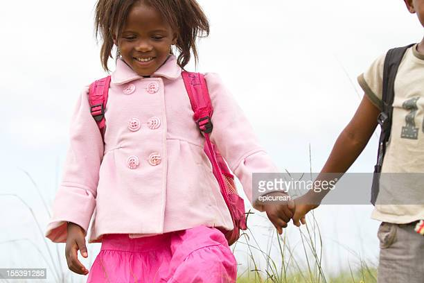 Happy South African girl smiling and holding her brothers hand