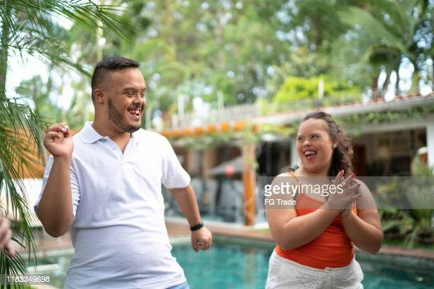 happy special needs couple dancing in backyard - down syndrome stock pictures, royalty-free photos & images