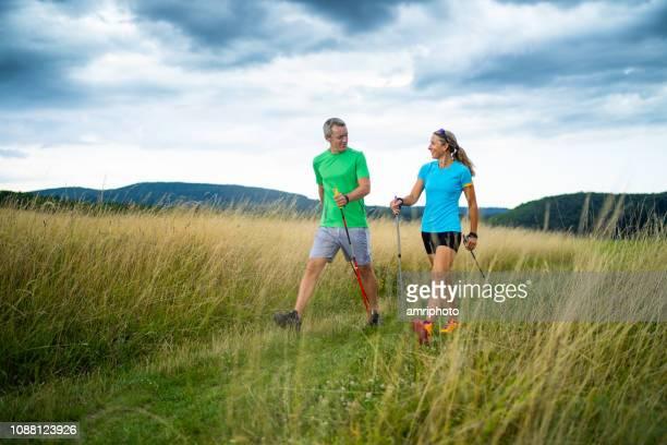 feliz pareja deportiva mirando sonriendo el uno al otro nórdico caminar juntos