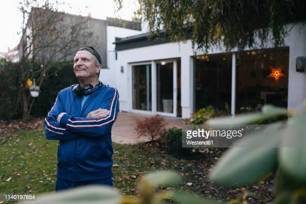 happy sportive senior man in tracksuit standing in garden - trainingsanzug stock-fotos und bilder