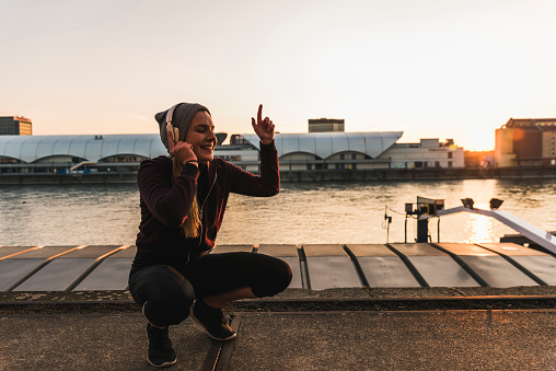 Happy sportive young woman listening to music at the riverside in the city at sunset - gettyimageskorea