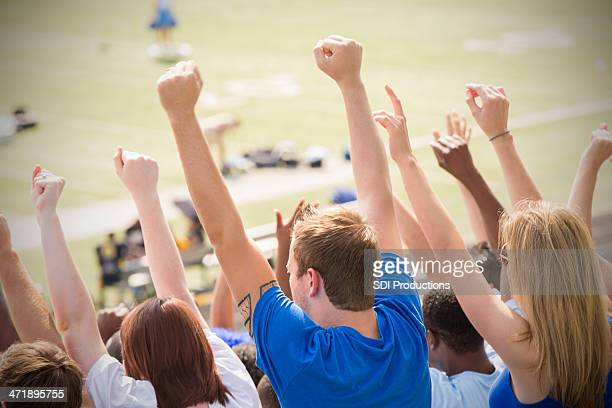 Happy sports fans cheering and celebrating in stadium stands