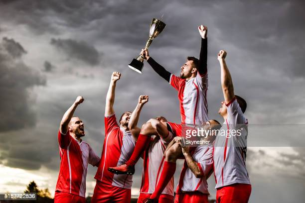 happy sports team celebrating their victory on a playing field. - the championship football league stock pictures, royalty-free photos & images