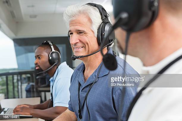 happy sportscasters watching and calling sports game in press box - commentator stock pictures, royalty-free photos & images