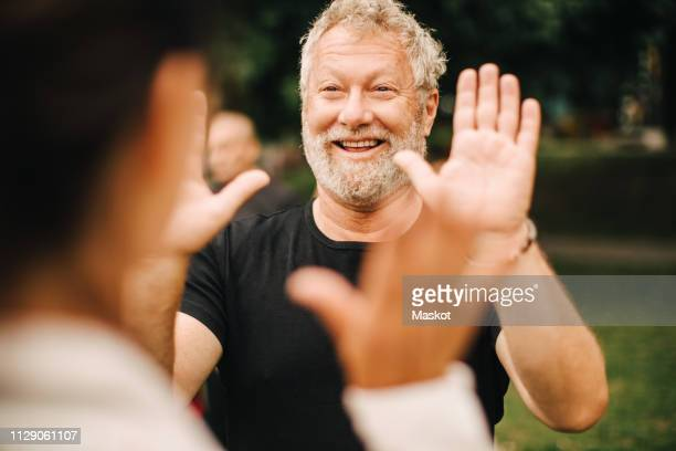 happy sporty man giving high-five to female friend while standing in park - high five stock-fotos und bilder