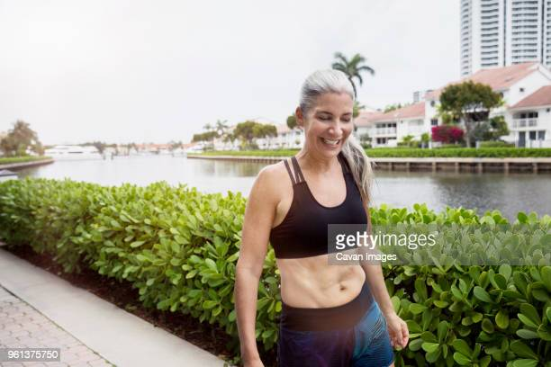 happy sporty mature woman walking on footpath by canal - aventura florida stock photos and pictures