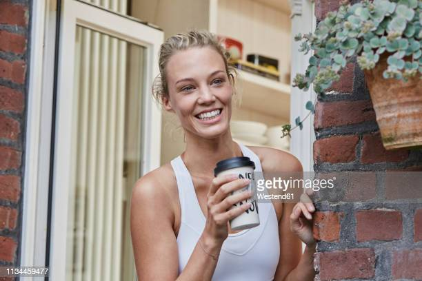 happy sporty young woman with takeaway drink at house entrance - finale wedstrijd stockfoto's en -beelden