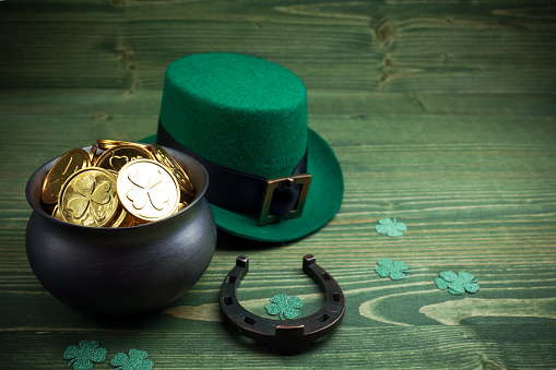 Happy St Patricks Day leprechaun hat with gold coins and lucky charms on vintage style green wood 1134171411
