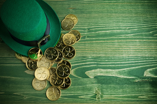Happy St Patricks Day leprechaun hat with gold coins on vintage green wood background 1132760101