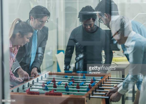 Happy start up team having fun while playing foosball on a break.