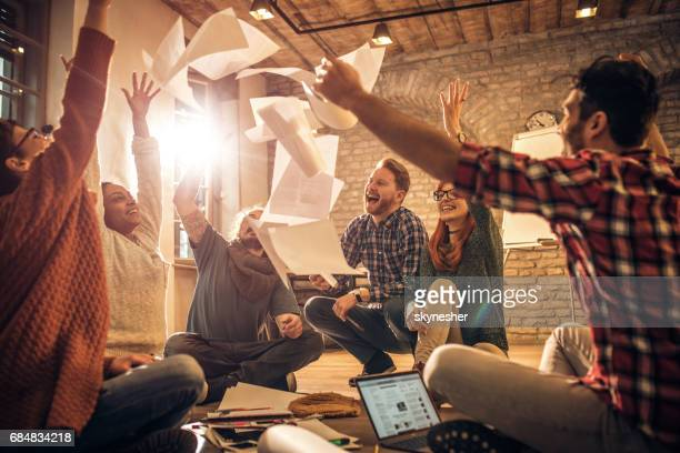 Happy start up team throwing papers in the air at casual office.