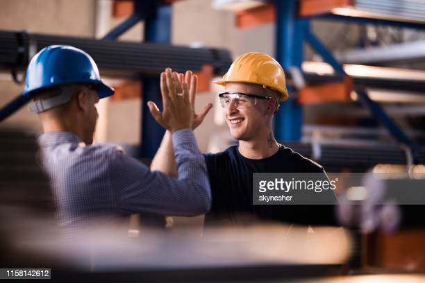 glücklicher stahlarbeiter und sein manager geben sich in einem lager. - industrieberuf stock-fotos und bilder