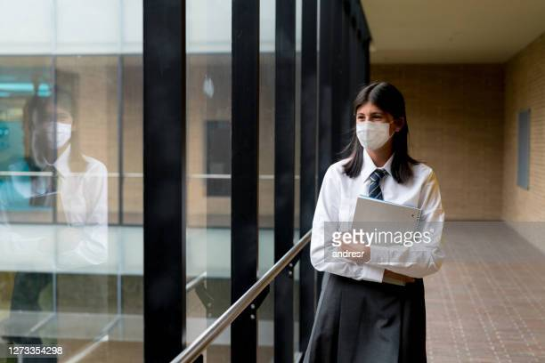 happy student at the school wearing a facemask to avoid an infectious disease - uniform stock pictures, royalty-free photos & images
