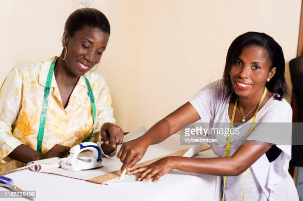 happy student draws a line on paper in the presence of her sewing teacher. - abidjan stock pictures, royalty-free photos & images