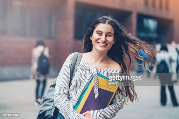Happy student holding textbooks