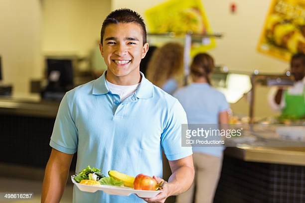Happy student holding tray of healthy food in school lunchroom