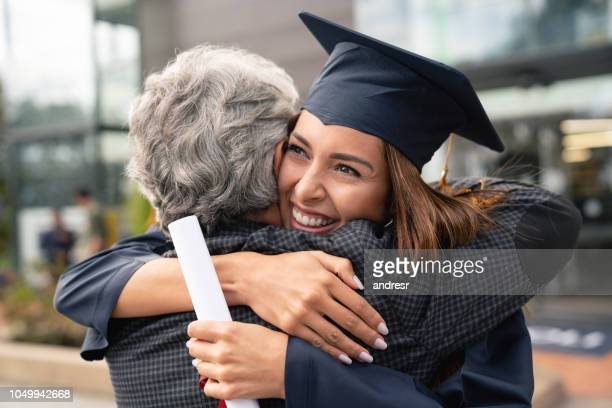 happy student hugging her father and celebrating her graduation - graduation stock pictures, royalty-free photos & images