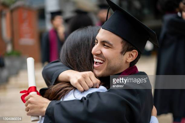 happy student hugging his mother on graduation day - alumni stock pictures, royalty-free photos & images