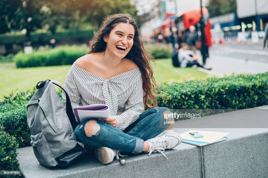 Happy student making homework outdoors in the city : Stock Photo