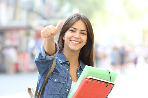 Happy student posing with thumbs up in the street 1030853182