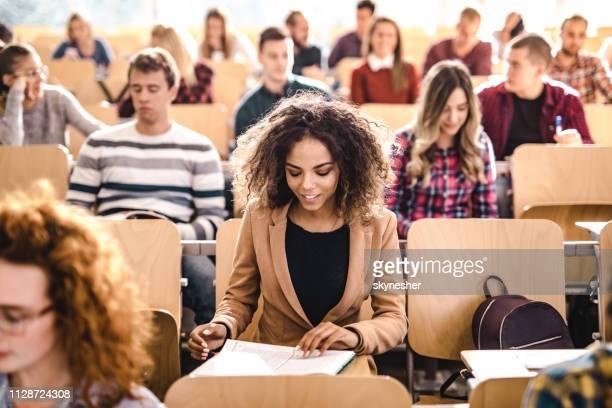 glückliche schüler lesen einen vortrag über eine klasse im unterricht. - schulische prüfung stock-fotos und bilder