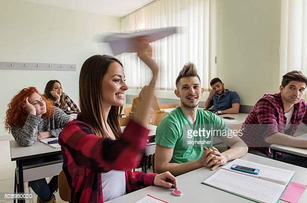Feliz estudiante tirando avión de papel en movimiento borroso.