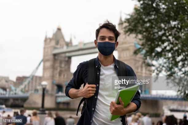 happy student wearing a facemask on the street in london - state of emergency stock pictures, royalty-free photos & images