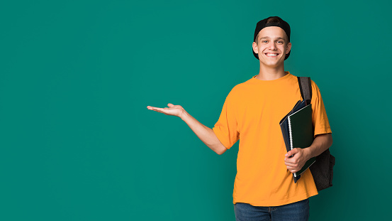 Happy student with books holding something on palm 1080915226