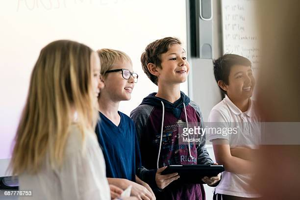 Happy students giving presentation with digital tablet in classroom
